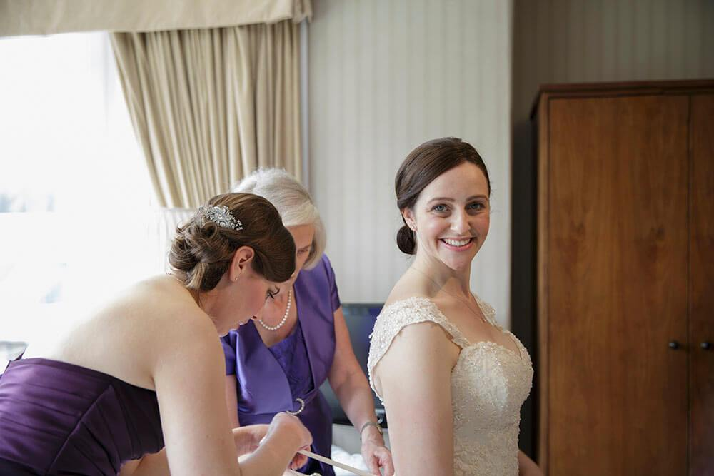 Bridal Prep - ©LouiseMallanPhotography - Bride getting helped into her dress by mum and bridesmaid